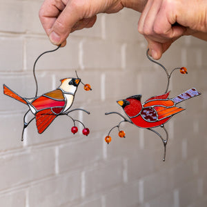Two cardinals sitting on branches with berries window hanging made of stained glass