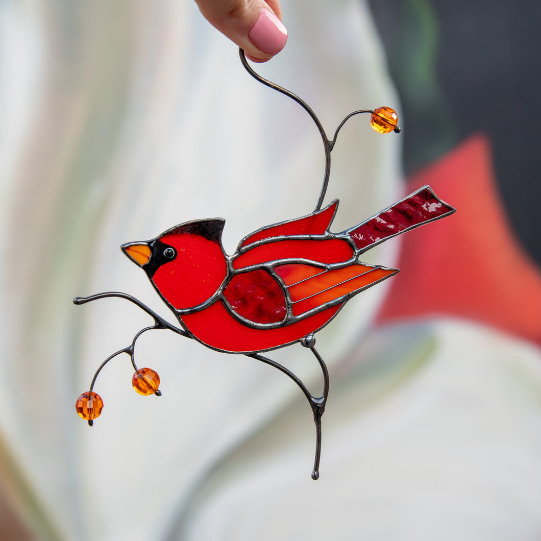 Stained glass male cardinal sitting on the branch window hanging