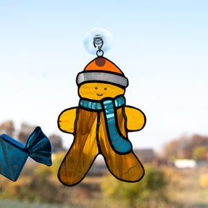 Cute stained glass cookie man wearing a hat and a blue scarf window hanging
