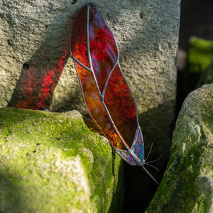 Stained glass red winter bird suncatcher with clear part in the lower part