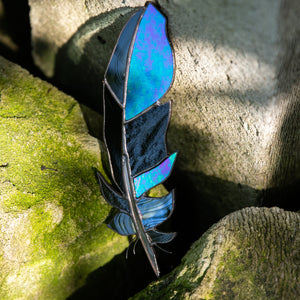 Window hanging of a stained glass raven feather
