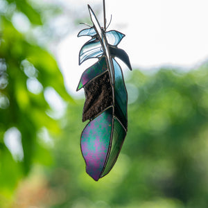 Suncatcher of a stained glass raven feather with modulating shades
