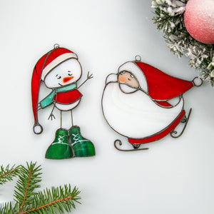 Two stained glass suncatchers of a snowman and santa  Edit alt text