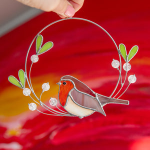 Robin bird of stained glass sitting on the wire mistletoe with leaves and berries