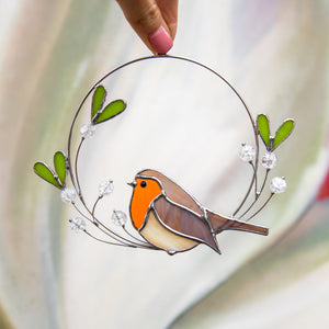 Stained glass robin sitting on the mistletoe suncatcher