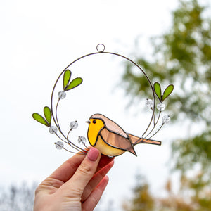 Stained glass suncatcher of robin sitting on the mistletoe