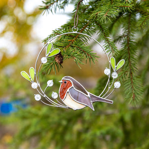 Stained glass robin on the mistletoe suncatcher used as a New Year Tree decoration