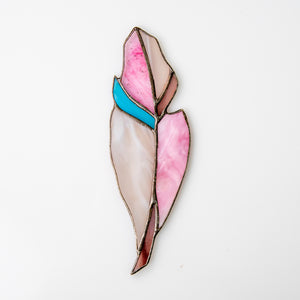 Suncatcher of a stained glass feather of pink colour with blue shade