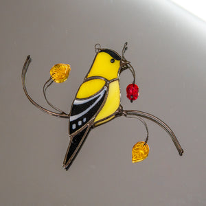 Stained glass goldfinch sitting on the branch with leaves and berries window hanging