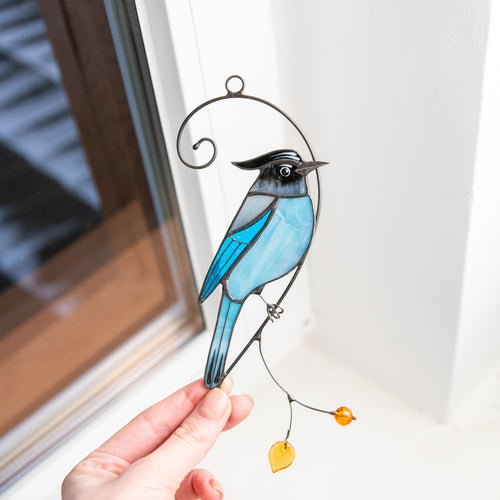 Stained glass Steller's Jay sitting on the branch with yellow leaf and berry suncatcher