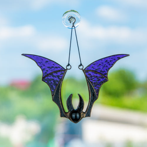 Window hanging of a stained glass purple-winged bat