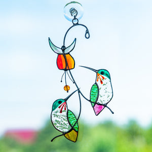 Stained glass hummingbirds on the branches with flower above suncatcher