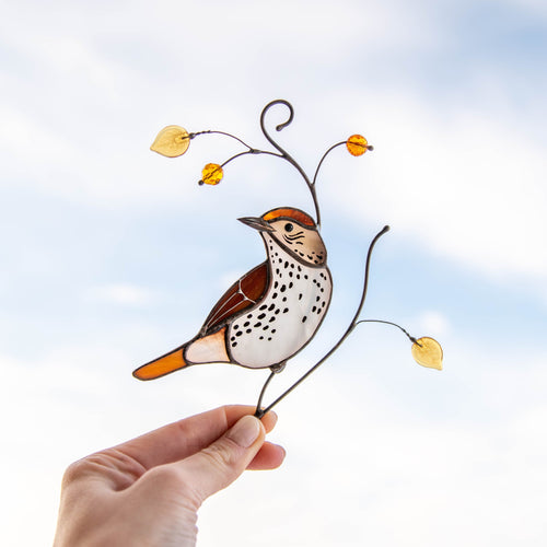 Stained glass brown thrasher bird sitting on the branch with yellow leaves and berries suncatcher