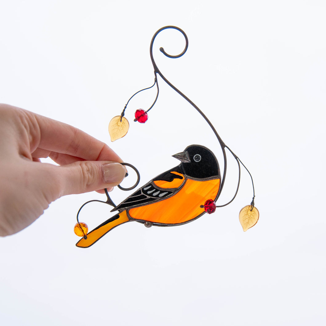 Stained glass Baltimore oriole bird suncatcher on the branch with leaves and berries