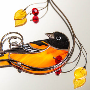 Zoomed stained glass suncatcher of Baltimore oriole bird