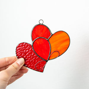 Stained glass suncatcher of two hearts united with each other
