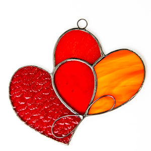 Stained glass suncatcher of two intertwined red hearts with the orange part