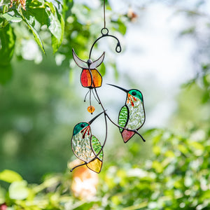 Stained glass hummingbirds sitting on the branch with the red flower above suncatcher