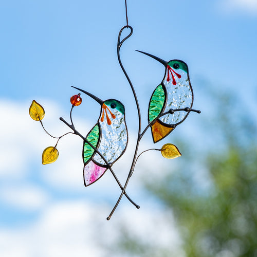 Stained glass hummingbirds sitting on the branch with leaves and berries suncatcher