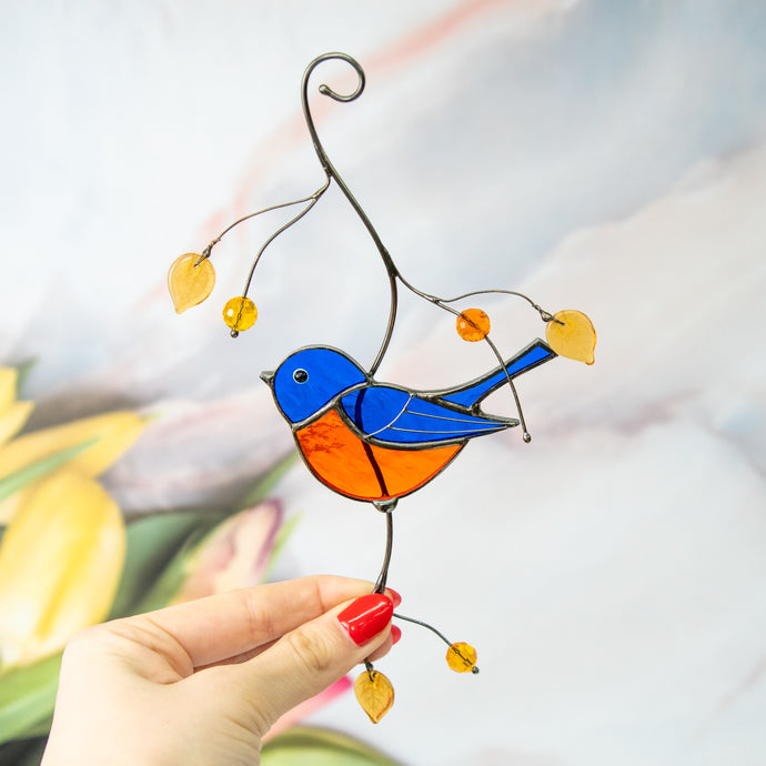 Stained glass bluebird sitting on the branch suncatcher