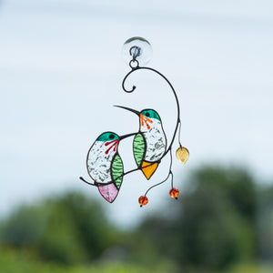 A pair of stained glass hummingbirds on the branch and looking in opposite directions suncatcher