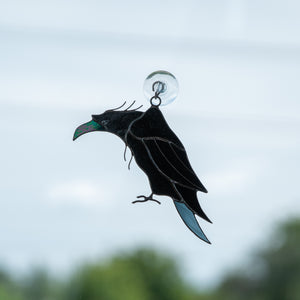 Suncatcher of a stained glass raven with nacre pecker