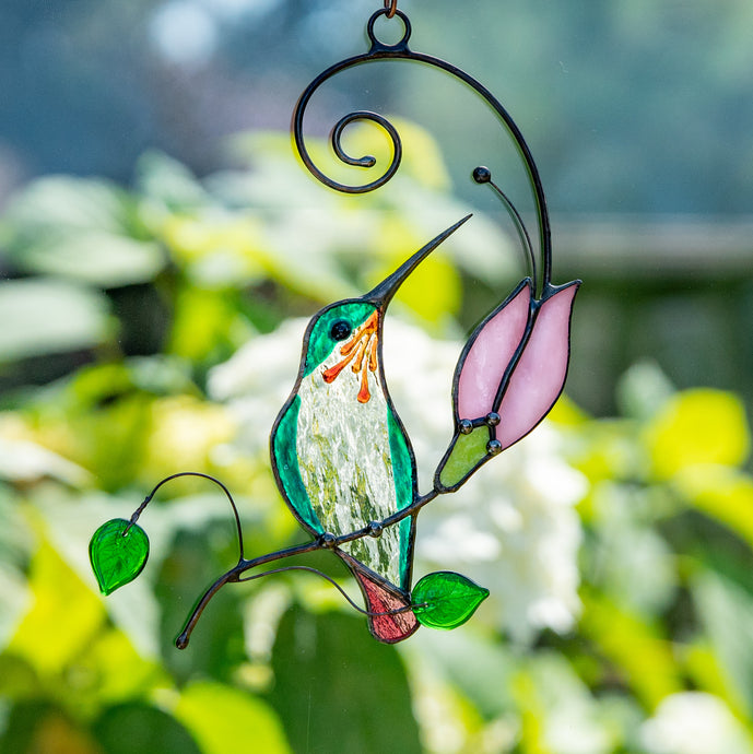 Stained glass hummingbird on the branch with pink flower suncatcher