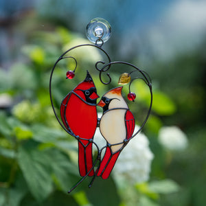 Stained glass of male and female Cardinals sitting on the heart-branch window hanging
