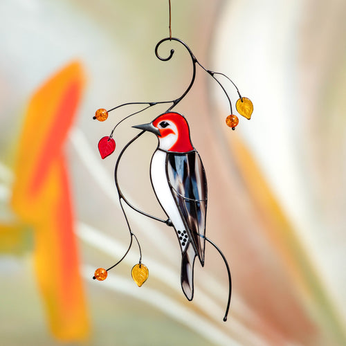 Stained glass woodpecker sitting on the branch with leaves and berries suncatcher