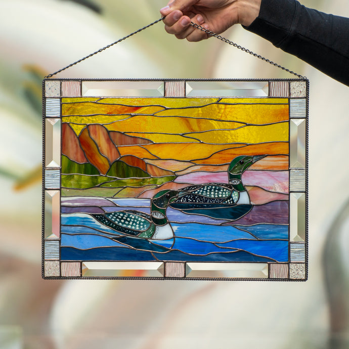 Stained glass panel depicting two ducks and the sunset