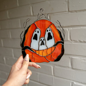 Stained glass ghost-eyed pumpkin window hanging for ghastly decor on Halloween