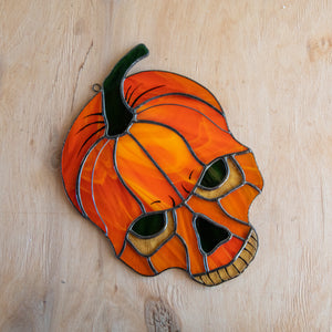 Stained glass pumpkin skull window hanging for ghastly Halloween decor