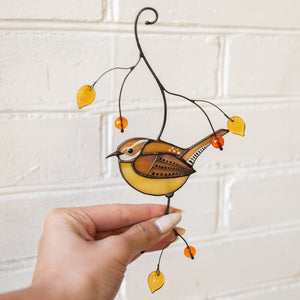 Stained glass window hanging of Carolina wren bird on the branch with leaves and berries