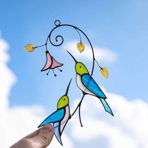 Sitting on the branch hummingbirds with a flower stained glass suncatcher