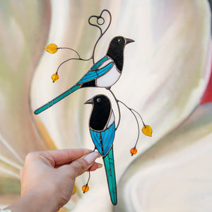 Stained glass suncatcher of two magpies sitting on the branch with leaves and berries