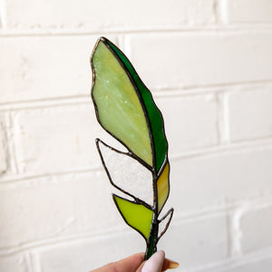 Suncatcher of a stained glass green feather with clear parts