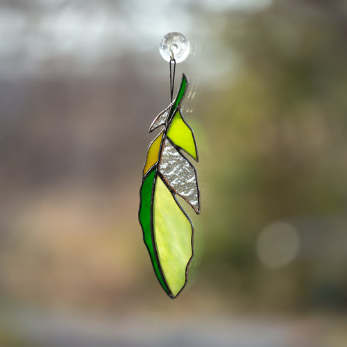 Stained glass feather of green colour with clear parts suncatcher