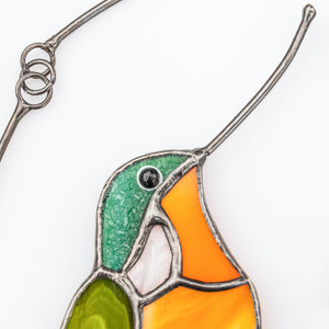 Zoomed stained glass hummingbird of orange and green shades window hanging