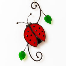 Load image into Gallery viewer,  Suncatcher of a stained glass ladybug with leaves