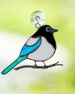 small fat magpie sitting on a branch stained glass suncatcher