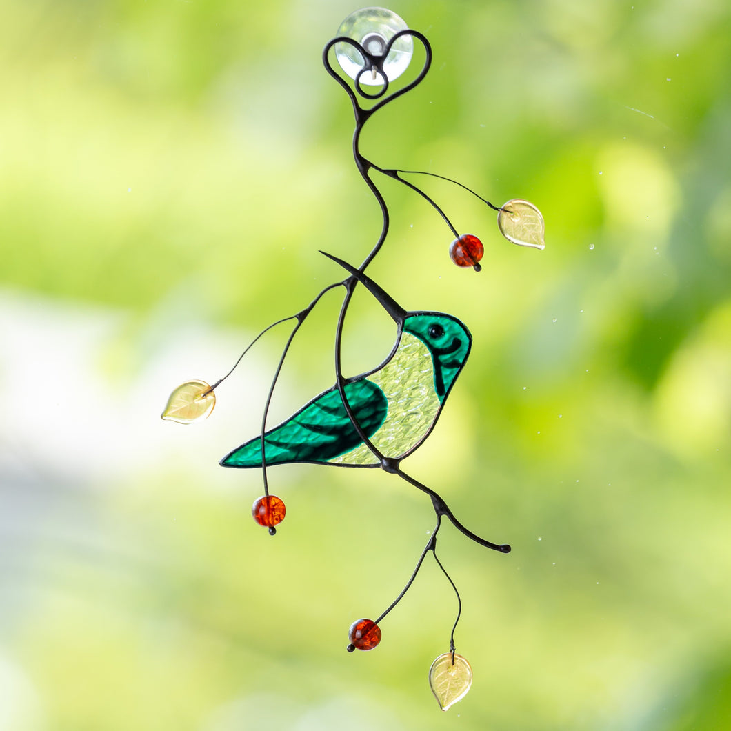 Stained glass green female hummingbird sitting on the branch with leaves and berries suncatcher