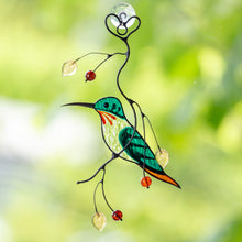 Load image into Gallery viewer, Green male hummingbird window hanging sitting on the branch with leaves and berries