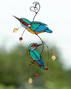 Two bright kingfishers on the wire branch made of stained glass