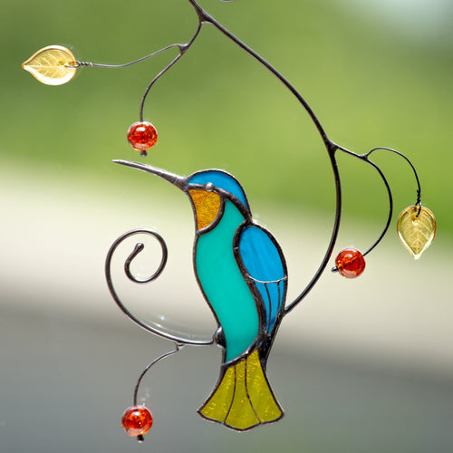 Stained glass bright hummingbird sitting on the branch window hanging