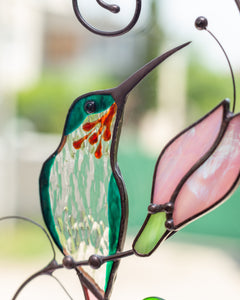 Tender stained glass hummingbird with pink flower