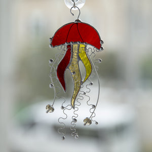Orange stained glass suncatcher of a jellyfish with yellow tentacles