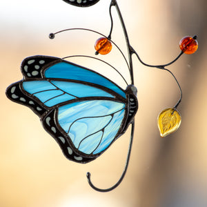 Zoomed stained glass suncatcher of a blue butterfly with leaves and berries