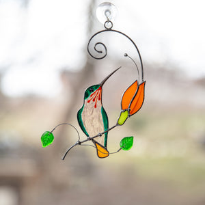 Suncatcher of a stained glass hummingbird on the branch with orange flower