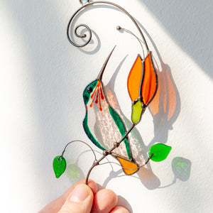 Window hanging of a stained glass hummingbird on the branch with orange flower