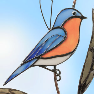 Zoomed stained glass bluebird sitting on the branch suncatcher